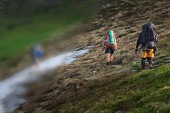 Hikers on the trail in the Islandic mountains. Trek in National Park Landmannalaugar, Iceland. valley is covered with bright green. Moss royalty free stock photography