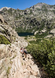 Hikers on trail between Lac de Capitello and Lac de Melo in Cors Stock Photo
