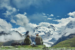Hikers on the trail in the mountains. Hikers on the trail in the Apls mountains. Trek near Matterhorn mount. Mountain ridge on the background Stock Images