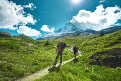 Hikers on the trail in the mountains. Hikers with backpacks on the trail in the Apls mountains. Trek near Matterhorn mount Stock Photos