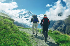 Hikers on the trail in the Swiss mountains. Hikers with backpacks on the trail in the Apls, Swiss mountains. Trek near Matterhorn mount, mountain ridge on Stock Photos