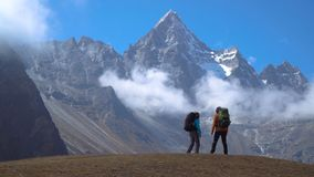 Hikers travel in the Himalayan mountains. Backpackers with backpacks travel in the Himalayan mountains. They look at the snowy peaks and are happy with the trip stock video