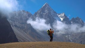 Hikers travel in the Himalayan mountains. Hikers with backpacks travel in the Himalayan mountains. They look at the snowy peaks and are happy with the trip. 4K stock footage