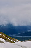 Hikers traversing a glacial snow mountain trail. Two distant hikers traversing a glacial snow mountain trail under a stormy Alaskan sky Stock Images