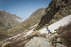 Hikers traversing snow near Lac de Melo in Corsica Stock Photos