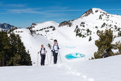 Hikers Trek Through a Snowy Mountain Landscape. A pair of hikers trek across a snowy mountain landscape stock photos