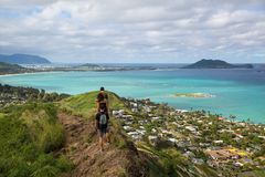 Hikers with the view of Lanikai from a top the Pillbox hiking tr. Hikers with the view of Lanikai from a top the Pillbox friends hiking trail Kailua Hawaii in stock photos
