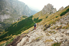 Hikers walking along a trail in rugged mountain terrain. Two young men in hiking gear wearing backpacks walking together along a rugged trail high up in the Royalty Free Stock Photo
