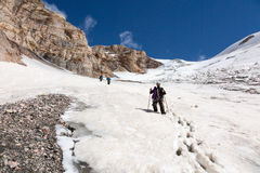 Hikers Walking Down on Snowfield. Group of Climbers Descending from Summit on Snow Trail Glacier with Alpine Climbing Gear Trekking Poles Deep Snow Blue Sky Rock Stock Image