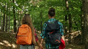 Hikers walking downhill in a forest - woman and teenage girl. Enjoy the woods in summer stock video