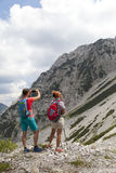 Hikers walking on hike in mountain nature landscape and taking photos Royalty Free Stock Images