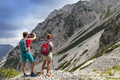 Hikers walking on hike in mountain nature landscape and taking photos Royalty Free Stock Photography