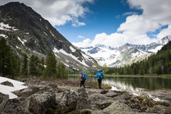 Hikers are walking by mountain lake Stock Photos