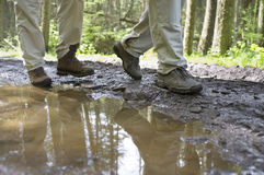 Hikers Walking Through Mud Puddle Royalty Free Stock Image