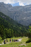 Hikers walking to the cirque of Gavarnie. People go on the hiking trail to falls of the cirque of Gavarnie. In the background there is a large rock amphitheater Stock Photo