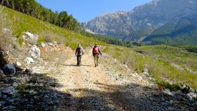 Hikers walking outdoors wearing hiker backpacks. Hikers walking to the Tahtali mountain peak in Turkey, Antalya province wearing hiker backpacks. Tahtali stock video footage