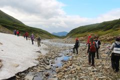 Hikers walks in mountains by river stock photography