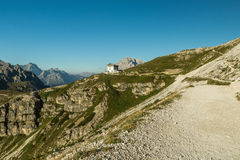 Hikers walks on a path in Drei Zinnen or Tre Cime di Lavaredo, Italian Dolomites. Rifugio Auronzo in backgroud. Travel concept, copy space, advertising Stock Images