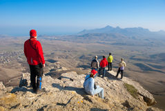 Hikers watch the terrain. From the peak of a cliff stock image