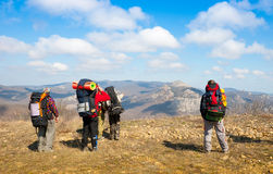 Hikers watch the terrain. From the peak of a cliff Stock Images