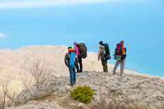 Hikers watch the terrain. From the peak of a cliff Stock Photography