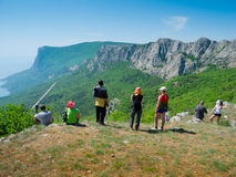 Hikers watch the terrain. From the peak of a cliff Royalty Free Stock Image