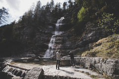 Hikers by waterfall in forest royalty free stock images