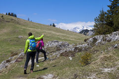 Hiking – Hikers walking on hike in mountain nature and pointing on mountain peak, on sunny day Royalty Free Stock Images
