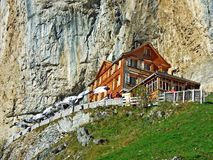 """Hiking and Ã""""scher cliff restaurant Ascher or Aescher cliff restaurant, Berggasthaus Aescher-Wildkirchli or Mountain inn Aescher. Hiking and Ã""""scher cliff royalty free stock photography"""