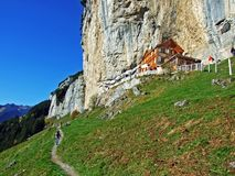"""Hiking and Ã""""scher cliff restaurant Ascher or Aescher cliff restaurant, Berggasthaus Aescher-Wildkirchli or Mountain inn Aescher. Hiking and Ã""""scher cliff royalty free stock photo"""