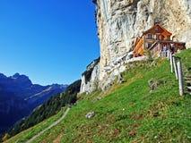 """Hiking and Ã""""scher cliff restaurant Ascher or Aescher cliff restaurant, Berggasthaus Aescher-Wildkirchli or Mountain inn Aescher stock photo"""