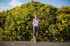 Hiking женщина представляя около желтых цветков Стоковые Изображения RF