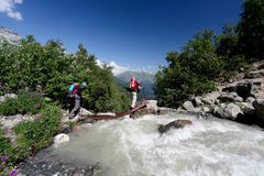 Hiking. Hiker in Caucasus mountains is crossing mountain river Royalty Free Stock Image
