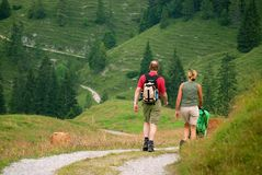 Hiking. Two people walking through green meadows with hills in the distance Stock Images