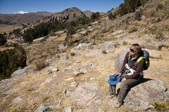 Hiking. A woman resting after a hike in the mountains of Bolivia near lake Titicaca stock photo