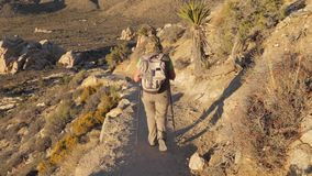 Active Woman Coming Down The Hill Along The Trail In The Mojave Desert Rear View. Hiking active women, dressed in sun protection clothing with a backpack and stock video
