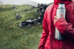 Hiking Adventure Tourism Vacation Holiday Concept. Unrecognizable girl traveler holds a thermos in her hand Overview of a wild la royalty free stock image