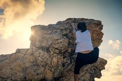Woman climbing to hill summit. Hiking Aian woman climb up to top hill during sunset. Sporty female climber to mountain summit peak against rays. Success concept Stock Photo