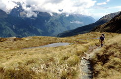 Hiking along a trail. Hiker with backpack on Routeburn Track, Fiordland NP, New Zealand.  Horizontal orientation Stock Photos
