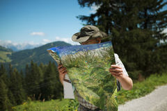 Hiking in the Alps. Man in Hiking gear studying a map looking for the direction while hiking in the european alps Royalty Free Stock Image