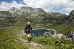 Hiking in the alps. Mature woman hiking in the Voralberg alps, Formarin see in the background Royalty Free Stock Photography