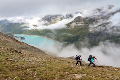 Hiking in Anniviers, Valais. A couple with backpacks hiking on a summer day in the Swiss alps near Grimentz, Switzerland, with turquoise lake lac de Moiry in the stock photography