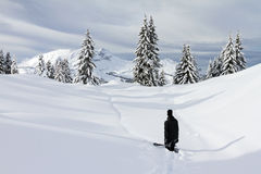 Hiking in the backcountry. Snowboarder hiking up the mountain in the fresh powder in the backcountry of Les Portes du Soleil stock image