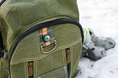 Hiking backpack color khaki with a compass behind. Hiking backpack color khaki with a compass behind Royalty Free Stock Photo