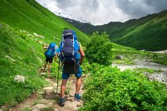 Hiking. Backpackers hiking in mountains. Mountain trekking. Men with backpacks on mountain trek. Hiking. Backpackers hiking in mountains. Mountain trekking. Men stock images