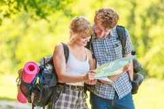 Hiking backpacking couple reading map on trip. Man and woman tourists backpackers reading map on trip. Young couple hikers searching looking for direction guide stock photo