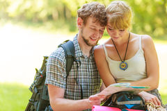 Hiking backpacking couple reading map on trip. Man and women tourists backpackers reading map on trip while resting. Young couple hikers searching looking for stock photo