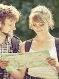 Hiking backpacking couple reading map on trip. Man and women tourists backpackers reading map on trip. Young couple hikers searching looking for direction guide stock photo