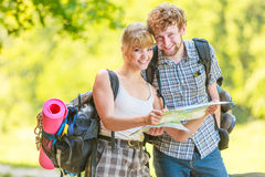 Hiking backpacking couple reading map on trip. Stock Image