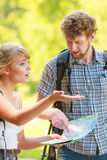 Hiking backpacking couple reading map on trip. Stock Photography